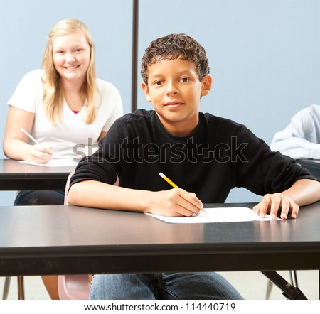 Handsome adolescent boy in school classroom, sitting at desk.