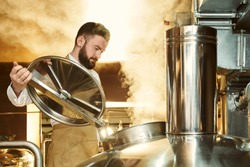 Handsome, adult brewer inspecting process of brewing beer with steam. Confident, bearded specialist opening cover of metallic brew kettle, looking down.