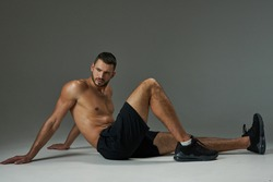 Handsome adult Caucasian sportsman in sportswear relaxing after training isolated on grey background
