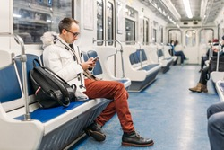 Handsome adult man in glasses with black backpack riding in subway train. In hands male hold smartphone. Social medias swallowed him up and he missed his stop. Internet addiction. Copy space.