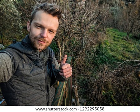 Handsome adult man making a self portrait with a thumb up #1292295058