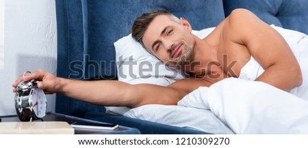 handsome adult man turning off alarm clock during morning time at home  #1210309270