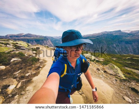 Handsome adventurous human taking selfie mountain. Woman traveler photo yourself action camera in nature. Travel Lifestyle adventure concept active vacations outdoor, hiking success and healthy life.