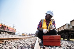 Handsome Africa American industrial engineering maintenance prepare and holding equipment for fix train at garage plants with wrench. Engineer and repair man concept. Safty first