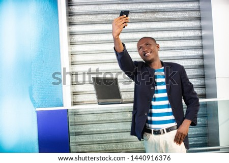 Handsome african adult man making selfie photo on cellphone camera while standing in city street in sunny summer day. Smiling man having an online video call on smartphone during free time outdoors #1440916376
