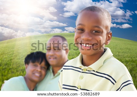 Handsome African American Boy with Proud Parents Standing Over Clouds, Sky and Arched Horizon of Grass Field.