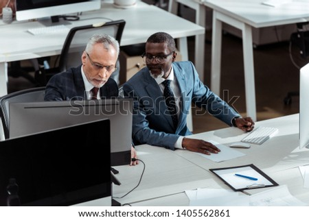 handsome african american businessman looking at computer monitor near coworker in office