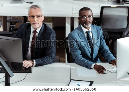 handsome african american businessman near coworker in office