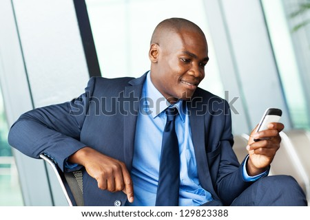 handsome african american businessman using smart phone emailing