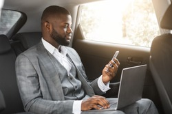 Handsome african american businessman with laptop holding smartphone while going by car on business trip, copy space. Black entrepreneur looking at mobile phone screen, using laptop