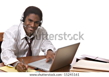 Handsome African-American businessman working on a laptop and wearing a headset