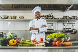 handsome african american chef standing at restaurant kitchen with crossed arms and looking at camera