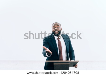 handsome african american lecturer standing at podium tribune and gesturing during seminar in conference hall #1204084708