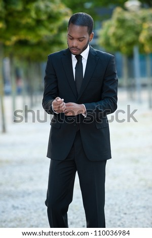 Handsome African American male fashion model adjusting his business suit.