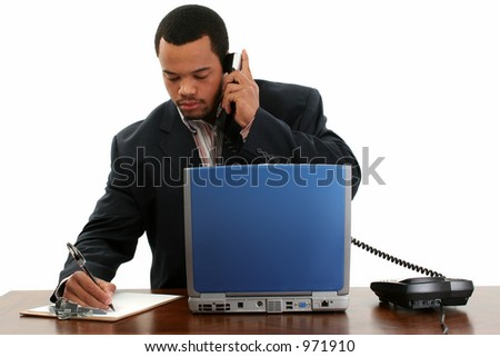 Handsome African American male writing at desk with laptop, phone, clipboard.