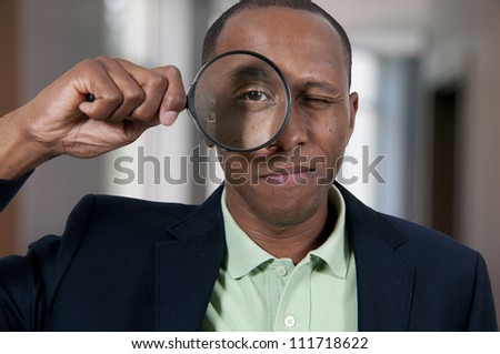 Handsome African American man looking through a large magnifying glass