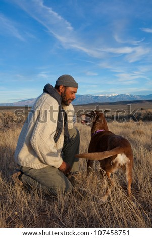Handsome African American man playing with his dog outdoors