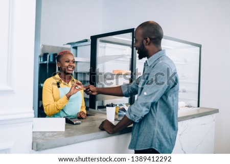 Handsome African American man smiling and giving credit card to friendly female barista while buying food in stylish modern cafe