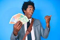 Handsome african american man with afro hair holding south african rand banknotes pointing thumb up to the side smiling happy with open mouth