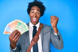 Handsome african american man with afro hair holding south african rand banknotes screaming proud, celebrating victory and success very excited with raised arms