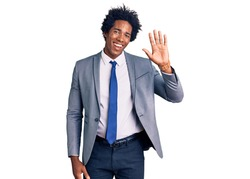 Handsome african american man with afro hair wearing business jacket waiving saying hello happy and smiling, friendly welcome gesture