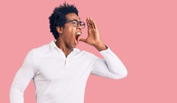 Handsome african american man with afro hair wearing casual clothes and glasses shouting and screaming loud to side with hand on mouth. communication concept.
