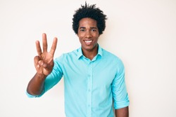 Handsome african american man with afro hair wearing casual clothes showing and pointing up with fingers number three while smiling confident and happy.