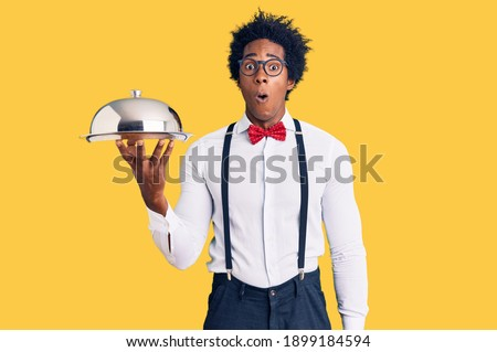 Handsome african american man with afro hair wearing waiter uniform holding silver tray scared and amazed with open mouth for surprise, disbelief face  Photo stock ©