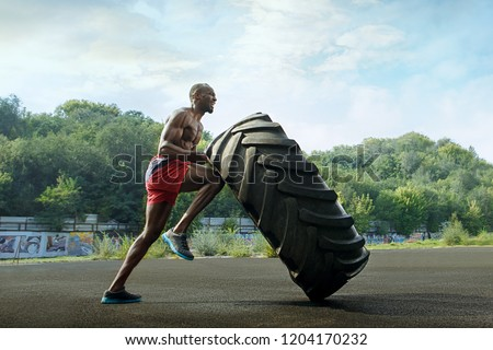 Handsome african american muscular man flipping big tire outdoor. #1204170232