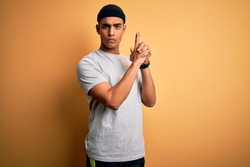 Handsome african american sportsman doing sport wearing sportswear over yellow background Holding symbolic gun with hand gesture, playing killing shooting weapons, angry face