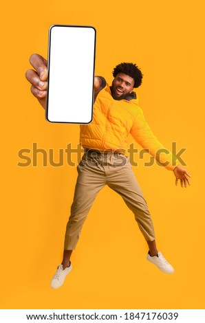 Handsome african american young man recommending new mobile application, collage. Excited black guy holding smartphone, showing blank screen, jumping up over orange studio background Foto stock ©