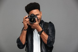 Handsome african guy with stylish haircut taking photo on digital camera, isolated on gray background