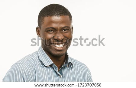 Handsome African guy with white-toothed smile looking at camera, dark-skinned well-dressed young man cut out on white background. Concept of dental care. Copy space at right. Toned image.