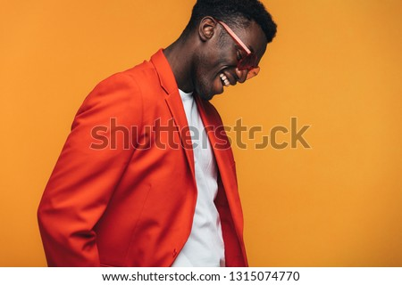 Handsome african male fashion model with sunglasses smiling against orange background. Stylish african man smiling in studio.