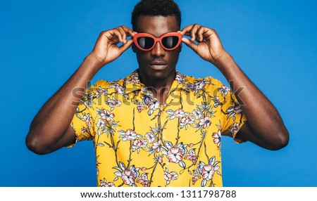 Handsome african man in a Hawaiian style with funky sunglasses against blue background. Young guy ready for a Hawaiian holiday. #1311798788