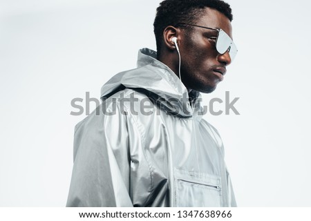 Handsome african man in silver hooded shirt, sunglasses and earphones against white background. Funky young african american man.