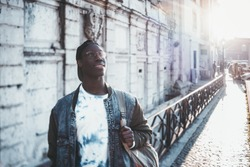 Handsome African student boy in a jean jacket and round glasses is looking upside while standing outdoor; male black undergraduate young guy on his way to university with copy space place for text
