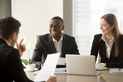 Handsome afro american businessman with beaming smile laughing on multi-ethnic international team meeting when partner telling joke, cheerful diverse business people having fun friendly atmosphere