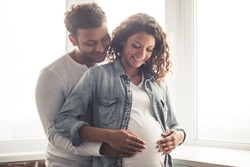Handsome Afro American man and his beautiful pregnant wife are hugging and smiling while standing near the window at home