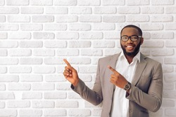 Handsome Afro American man in classic suit and glasses is smiling, looking at camera and pointing away, against white brick wall
