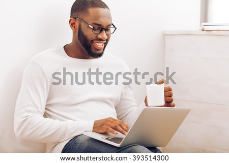Handsome Afro American man in glasses is using a laptop, holding a cup and smiling while working at home