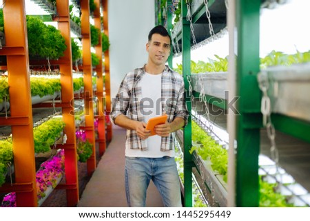 Handsome agronomist. Handsome agronomist wearing squared shirt standing near shelves with plants #1445295449