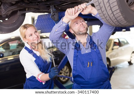 Handsome american mechanic and female assistant working at auto repair shop