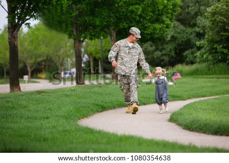 Handsome American Soldier in uniform having fun with his 2 year old daughter