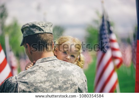 Handsome American Soldier in uniform holding his cute 2 year old daughter