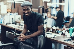 Handsome and attractive barber master looking at camera standing against blurred barbershop