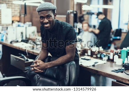 Handsome and attractive barber master looking at camera standing against blurred barbershop Photo stock ©