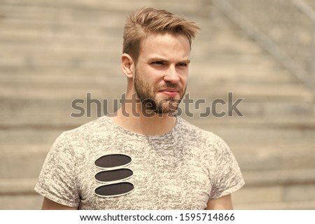 Handsome and attractive. Handsome man in summer style on sunny day. Caucasian guy with sexy beard on unshaven handsome face and stylish blond hair on urban outdoor. Casual and handsome.