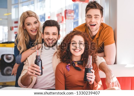 handsome and beautiful friends holding glass bottles with drink and looking at camera