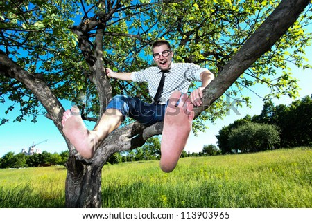 Handsome and cheerful young man in glasses sitting on a tree branch with bare feet close-up - stock photo